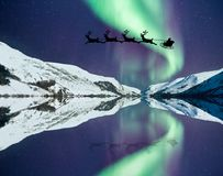 Santa Claus with flying reindeer. And sleigh silhouette. Northern lights over water and snow covered mountains like Lapland or the North Pole royalty free stock photo