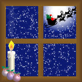Santa claus flying in the sky. View trhough the window with a candle of santa claus fliying in the sky with the moon behind Royalty Free Stock Image