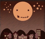 Santa Claus flying upper city beside Moon Stock Images