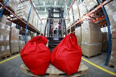 Santa Claus forklift operator in warehouse. Santa Claus as a forklift operator at work in warehouse. 2 large red sack at the front of forklift.fish-eye lens Royalty Free Stock Photo