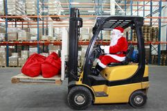 Santa Claus  forklift operator  in warehouse. Santa Claus as a forklift operator at work in warehouse. 2 large red sack at the front of forklift.profile view Royalty Free Stock Photo
