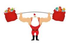 Santa Claus forte tenant le sac de barbell et de cadeau Photo libre de droits