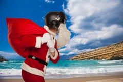 Santa Claus fraîche avec des cadeaux d'un sac dans le casque de jets Image stock