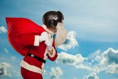 Santa Claus fraîche avec un sac des cadeaux dans des jets Photographie stock
