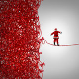 Santa Claus Freedom. And holiday management gift giving crisis as a concept with santaclause as a tightrope walker walking out of a confused tangled chaos of Royalty Free Stock Photo