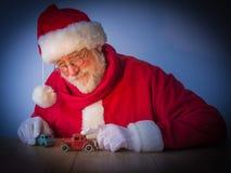 Santa Claus gaie joue avec des jouets dans la lumière lumineuse Photographie stock