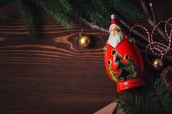 Santa Claus, garneringar och gran förgrena sig på en trätabell Arkivfoton
