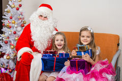 Santa Claus gave presents to children, and together looked in the frame Stock Images