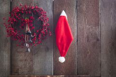 Santa Claus-geïsoleerde helperhoed en kroon van Kerstmis de rode bessen handmande op de houten omheining als achtergrond Royalty-vrije Stock Fotografie