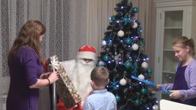 Santa Claus geeft voorstelt aan kinderen stock videobeelden