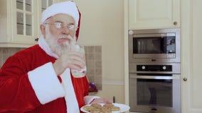 Santa Claus genießen vom Essen von frischen Plätzchen und von Trinkmilch stock video