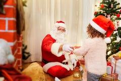 Santa Claus ger barnet en gåva för jul inomhus i en ro Royaltyfria Bilder
