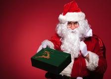 Santa Claus ger dig en grön närvarande ask Arkivbild