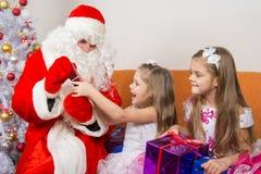 Santa Claus ger gåvor två systrar Royaltyfri Foto