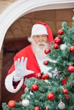 Santa Claus Gesturing From Christmas Tree Imagem de Stock Royalty Free