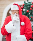 Santa Claus Gesturing Finger On Lips Stock Afbeelding