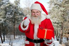 Santa Claus gesturing thumb up outdoors. Stock Image