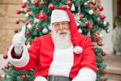 Santa Claus Gesturing Thumbsup Against Christmas. Portrait of happy Santa Claus gesturing thumbsup against Christmas tree Stock Images