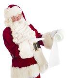 Santa Claus Gesturing At Wish List. Portrait of Santa Claus gesturing at wish list against white background Stock Image