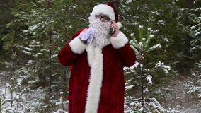 Santa Claus with gift bag talking on smartphone in snowy forest stock video footage