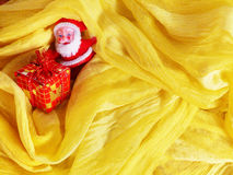 Santa Claus and gift box. On yellow background Stock Image