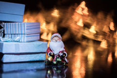 Santa Claus with gift box on the background of colorful bokeh in the form of Christmas trees Stock Images