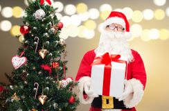 Santa claus with gift box at christmas tree. Holidays and people concept - man in costume of santa claus with gift box at christmas tree over lights background Stock Photography