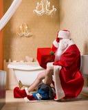 Santa Claus with gift box sitting on the toilet Stock Photos