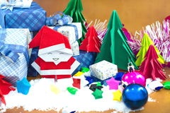 Santa Claus and gift box with small star paper on the snow field Royalty Free Stock Photo