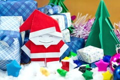 Santa Claus and gift box with small star paper on the snow field Royalty Free Stock Photos