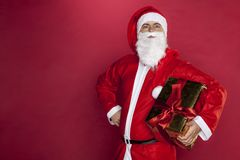 Santa Claus with a gift in his hand, copy space next to him. On the red background stock images