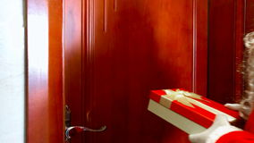 Santa Claus with gift knocking the door and saying hello