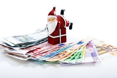 Santa Claus on gift lying on fanned euro notes Stock Image