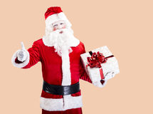 Santa Claus with gift posing on color background. Funny Santa Claus with gift standing in front of color background Stock Photography