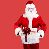 Santa Claus with gift posing on red background. Santa Claus with gift posing on color red background Royalty Free Stock Images