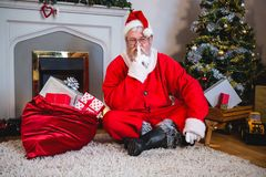 Santa claus with gift sack sitting on rug with finger on lips in living room Stock Photo