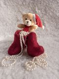 Santa Claus Gift to Christmass. Soft toy bear cub with a Christmas boot and pearls on a snowy background Stock Photography
