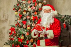 Santa Claus with giftbox on background of sparkling firtree stock image