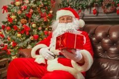 Santa Claus with giftbox on background of sparkling firtree. Chr stock photography
