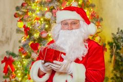 Santa Claus with giftbox on background of sparkling firtree stock images