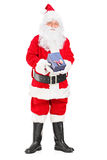 Santa Claus with a giftbox in his hands. Full length portrait of a happy Santa Claus with a giftbox in his hands on white background royalty free stock image