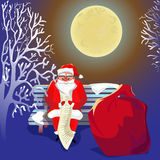Santa Claus with gifts. Christmas. New Year. Celebration. Santa Claus sits on a bench in the park under the moonlight, and check the list with gifts Royalty Free Stock Photography