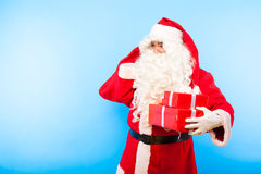Santa claus with gifts on hands on blue background stock photo