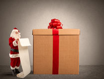 Santa Claus with gifts list. And a big present box Royalty Free Stock Images