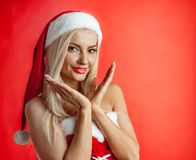 Santa claus girl. Beautiful santa claus girl on red christmas background Royalty Free Stock Photography