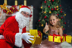 Santa Claus and a girl in a dress. Christmas Scenes. The child hugging Santa Stock Image