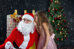Santa Claus and a girl in a dress. Christmas Scenes. The child whispers into the ear of Santa about their wish to get a gift for Christmas Stock Image