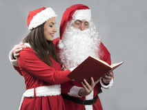 Santa claus and  girl elf  reading wish book Stock Photography
