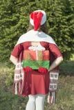 Santa Claus girl hidding Christmas presents Stock Photos