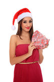 Santa claus girl holding a box. Girl with dress and santa claus hat holding a heart shape box Royalty Free Stock Image